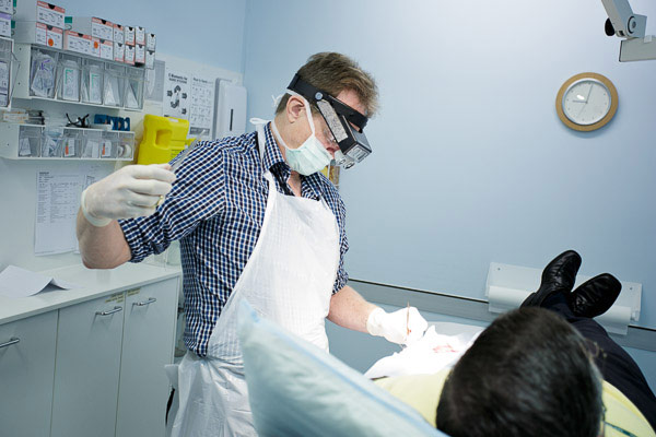 Doctor stitching up after performing an excision of a skin cancer in our dedicated skin theatre