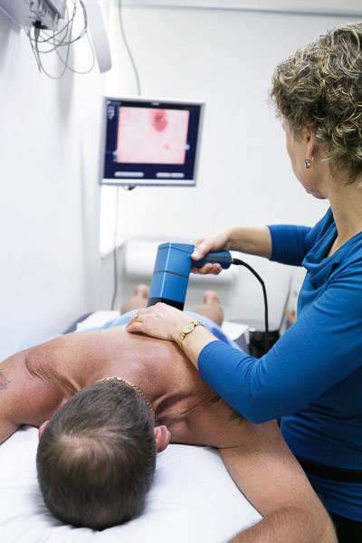 Doctor using MoleMax machine to image a pigmented mole during a skin cancer check